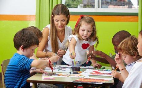 Kindergarten Kinder malen mit bunten Wasserfarben an ihren Bildern. Die Erzieherin macht auch mit.