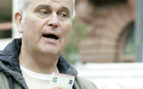 Ein Mann hält einen Zehneuroschein hoch.