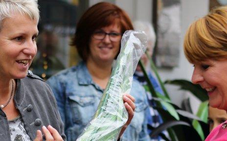 Zwei Frauen halten einen Dekoartikel in den Händen und unterhalten sich auf dem Hökermarkt darüber