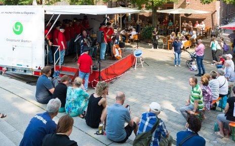 ZuschauerInnen vor einer Bühne mit Musikern auf dem Kajenmarkt.