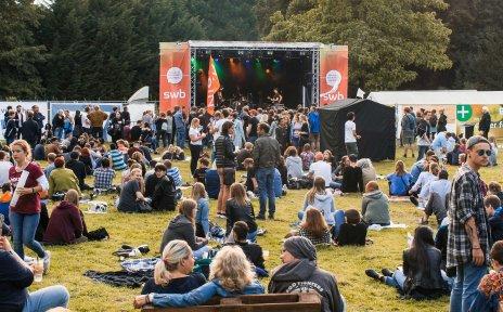 Viele Menschen sitzen auf Paletten vor einer Bühne.