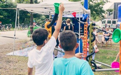 Oslebshauser Dorffest: Kinder stehen mit dem Rücken zur Kamera, vor Ihnen ist Pavillon mit einer selbstgebauten Rohrbahn für Bälle.