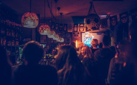 Ein Mann hält in einer vollen Bar einen Vortrag.