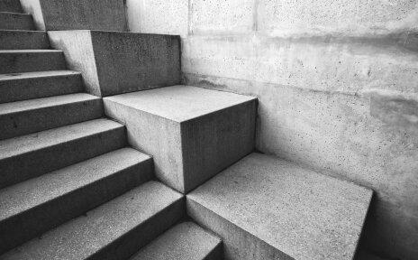 Treppenstufen aus grauem Stein, die entlang einer Wand führen