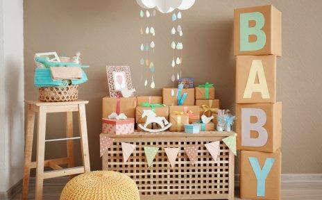 Eine Holzbox auf der eingepackte Geschenke liegen. Rechts von der Holzbox stehen übereinander gestapelte Boxen auf denen das Wort Baby steht. Auf der linken Seite steht ein Holzstuhl mit Handtüchern und einem Stoff-Dinosaurier drin.