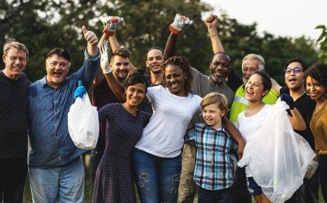 Ein Gruppe bestehend aus 12 Menschenfreut sich und streckt die Arme in die Luft. Sie tragen Arbeitshandschuhe und Mülltüten