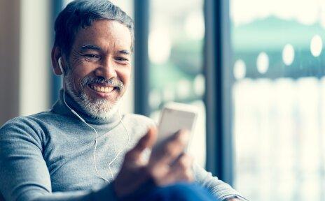Ein Mann sitzt vor einem großen Fenster, trägt Kopfhörer und blickt auf sein Handy