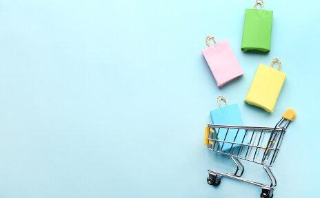 Über einem kleinen Einkaufswagen schweben gebastelte Einkaufstüten. Der Hintergrund ist türkis.