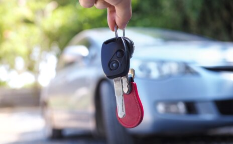 Jemand hält einen Autoschlüssel, im Hintergrund ist verschwommen ein Auto zu sehen