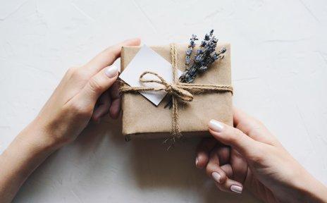 Auf weißem Hintergrund halten zwei Hände ein Geschenk, das in braunem Papier eingewickelt ist und mit einer Kordel, Lavendel und einer kleiner karte dekoriert wurde.
