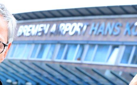 Ein Mann mit runder Brille und Krawatte zeigt auf den neuen Namen am Flughafenterminal