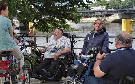 Eine Gruppe von Menschen in Rollstühlen, mit Handbike und Dreirad an der Weser.