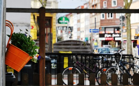 Ein orangefarbener Blumentopf mit weiß blühenden Blumen an einem Geländer hängend, im Hintergrund die Sielwallkreuzung