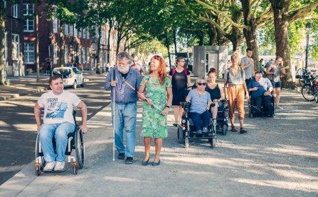 Eine Menschengruppe an der Schlachte. Einige von ihnen sind blind oder sitzen im Rollstuhl.