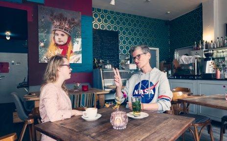 Zwei Frauen unterhalten sich in Gebärdensprache. Sie sitzen an einem Tisch in einem Café.