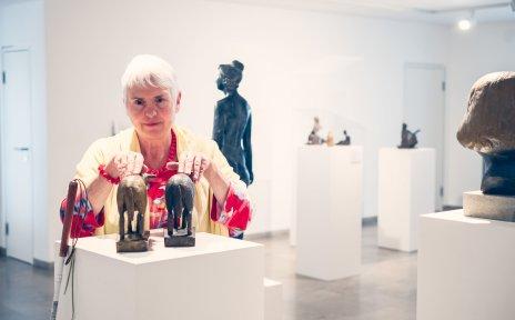 Eine blinde Frau ertastet zwei Skulpturen in einer Austellung.