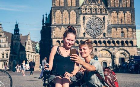 Zwei Frauen auf dem Bremer Marktplatz. Sie machen ein Selfie mit ihrem Smartphone, im Hintergrund ist der Bremer Dom zu sehen. Eine von den beiden Frauen sitzt im Rollstuhl.
