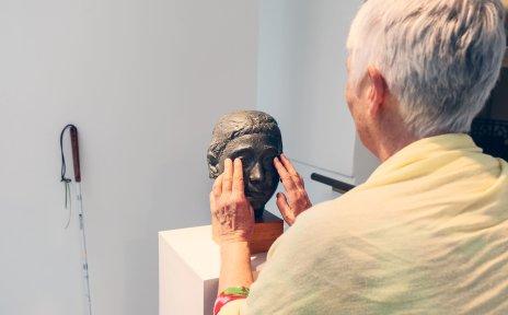 Eine Frau ertastet die Augen einer Bronzefigur in Form eines Frauenkopfes in einer Austellung.