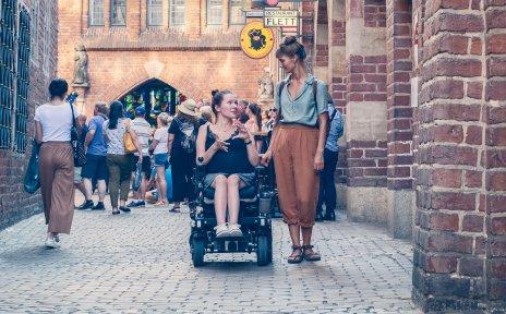 Zwei Frauen in der Böttcherstraße. Eine von ihnen sitzt im Rollstuhl.