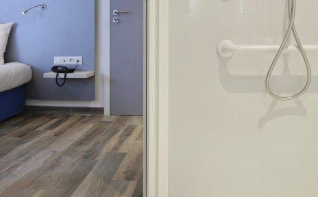 Blick in eine barrierefreie Dusche mit Duschsitz, im Hintergrund ein Hotelzimmer.