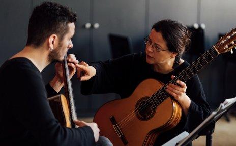 Ein Mann und eine Frau sitzen in einem Raum und haben Gitarren in der Hand. Die Frau erklärt dem Mann etwas an der Gitarre.