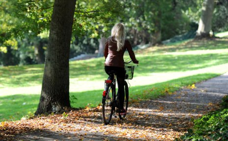 Eine Fahrradfahrerin fährt durch den Knoops Park