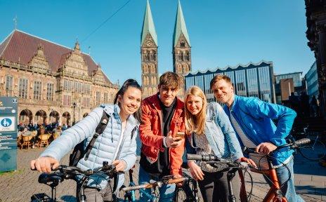 Vier junge Menschen mit ihren Fahrrädern am Bremer Marktplatz