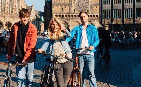Junge Menschen schieben auf dem Bremer Marktplatz ihre Räder