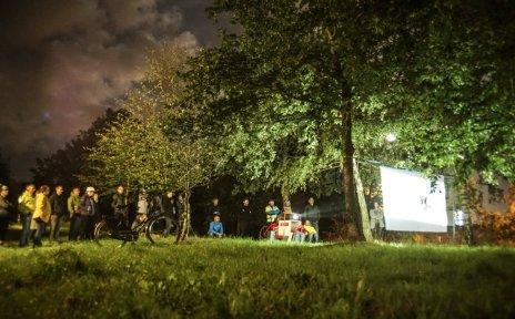 Eine Menschengruppe steht nachts auf einer Wiese und schaut einen Film, der auf eine zwischen zwei Bäume gespannt Leinwand projiziert wird. Im Vordergrund steht ein Fahrrad.