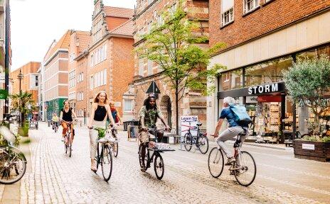 Eine Gruppe von Radfahrerinnen und Radfahrern fährt die Langenstraße auf Höhe des Kontorhauses entlang