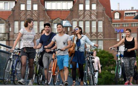 Junge Menschen laufen über eine Brücke und schieben ihre Fahrräder neben sich her