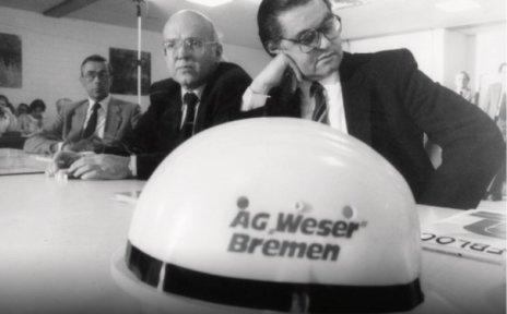 Drei Männer sitzen an einem Tisch, alle haben Brillen auf. Vor ihnen liegt ein Helm, auf dem AG Weser Bremen steht. Das Bild ist schwarz weiß.