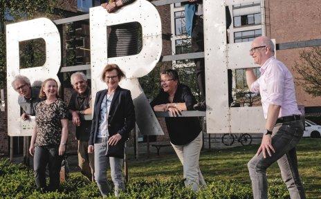 Einige Menschen, stehen an dem Bremen Schild in der Überseestadt und lächeln.