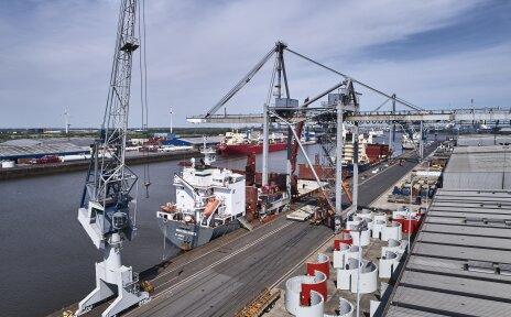 Zu sehen ist der Neustädter Hafen. Ein großes Containerschiff hat angelegt. Zudem sind einige Kräne, das Wasser und eine Lagerhalle zu sehen. In einiger Entfernung befinden sich noch zwei weitere Containerschiffe.