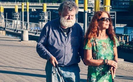 Ein Mann und eine Frau, beide mit Blindenstock, gehen an einem Fluss spazieren. Im Hintergrund sind Schiffe und eine Brücke zu sehen.