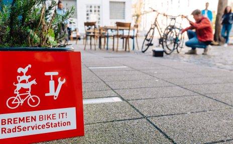 Logo Bremen BIKE IT! Rad Service Station. Im Hintergrund wird ein Fahrrad repariert.