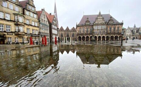 Historische Gebäude spiegeln sich auf einer nassen Fläche.