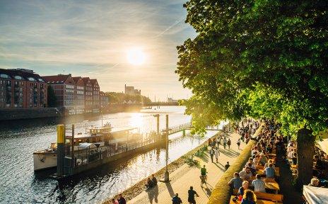 Blick auf Schiffe, schlenderte Menschen und Biergärten an der abendlichen Weserpromenade Schlachte