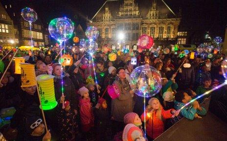 Laternenumzug am Abend: Zahlreiche Menschen stehen mit Laternen auf dem Bremer Marktplatz vor dem Rathaus.