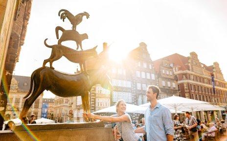 Eine Frau umfasst die Füße des Esels der Bremer Stadtmusikanten. Sie lächelt dabei einen Mann an.