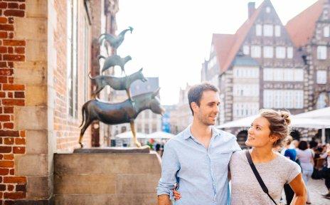 Eine Frau und ein Mann stehen vor den Bremer Stadtmusikanten.