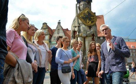 Ein Gästeführer erzählt einer jungen Gruppe bei einer Stadtführung am Roland Wissenswertes über Bremen