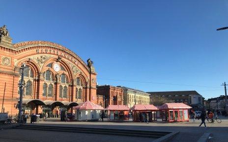 Vor dem Hauptgebäude des Bremer Hauptbahnhofes stehen rote Losbuden.