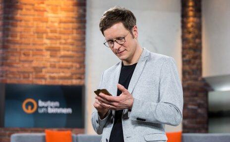 Der buten un binnen-Moderator Felix Krömer wurde im buten un binnen-TV-Studio abgelichtet, während er sein Smartphone in der Hand hält.