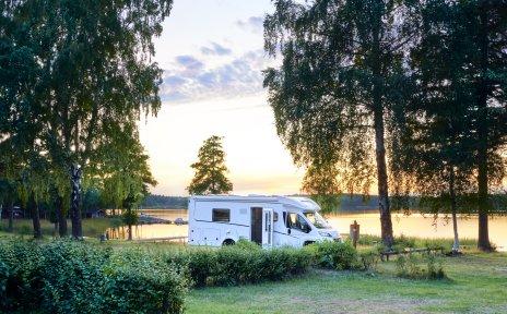 Ein Wohnmobil steht zwischen mehreren Bäumen auf einer Wiese an einem See bei Sonnenuntergang. Rechts im Bild sieht man ein kleiner rotes Holzhaus mit einem Rettungsring.