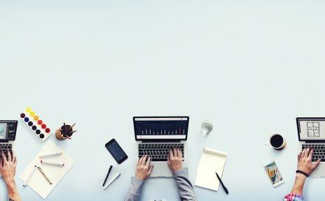 Drei Laptops stehen auf einem Tisch