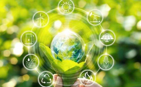 Kampagnenbild zum Starthaus Crowdfunding: Eine Hand hält grüne Blätter, in denen eine Seifenblase liegt, die einem durchsichtigen Globus ähnelt. Darum sind kreisförmig mehrere Grafiken angeordnet, die verschiedene industrielle Symbole zeigen. Der Hintergrund ist grün.