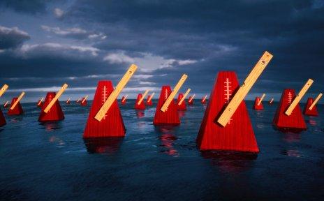 Mehrere rote Metronome im Wasser