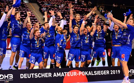 Eine Gruppe von Männern mit blauen Handballtrikots freut sich.