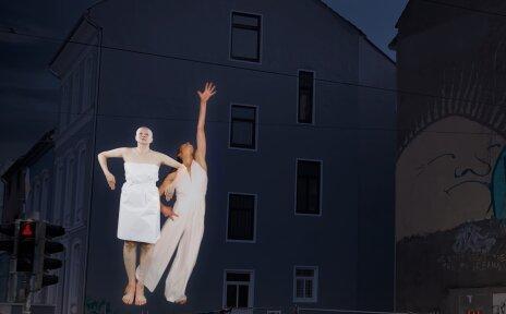 Die Bilder von Tänzer*innen werden an eine Hausfassade im Bremer Viertel projiziert.